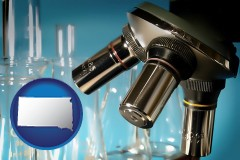 south-dakota map icon and a microscope and glassware in a research laboratory