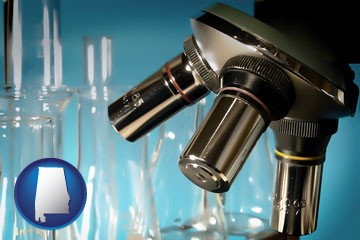 a microscope and glassware in a research laboratory - with Alabama icon