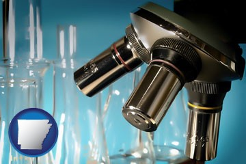 a microscope and glassware in a research laboratory - with Arkansas icon