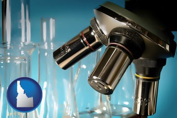 a microscope and glassware in a research laboratory - with Idaho icon