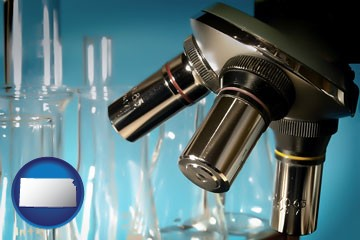 a microscope and glassware in a research laboratory - with Kansas icon