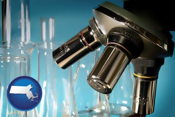 a microscope and glassware in a research laboratory - with Massachusetts icon