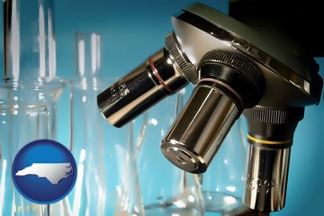 a microscope and glassware in a research laboratory - with North Carolina icon
