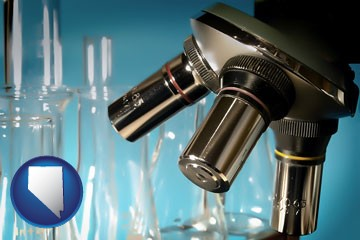 a microscope and glassware in a research laboratory - with Nevada icon