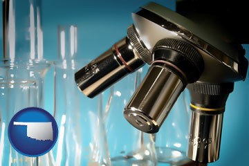a microscope and glassware in a research laboratory - with Oklahoma icon