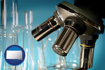 a microscope and glassware in a research laboratory - with South Dakota icon