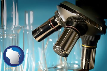 a microscope and glassware in a research laboratory - with Wisconsin icon